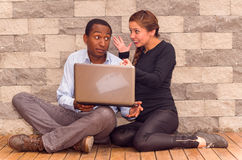 Charming young interracial couple sitting by brick wall with laptop interacting and having fun stock photography