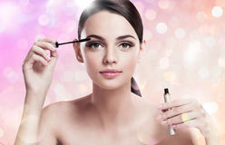 Charming young lady applying mascara Royalty Free Stock Image
