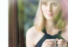 Charming young lady in black dress and with cup. Stock Images