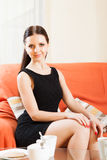 Charming young lady in black on  sofa. Girl in black dress sitting on  sofa Stock Image