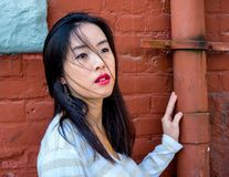 Contrast of a pretty woman by brick wall and downspout. Charming young lady poses by old building with her hand on a downspout and a deep dark red wall stock photography