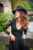 Charming young light brown hair brunette woman with big black hat and blouse with lace sleeves. gorgeous young woman with cur. Ly hair posing. Beautiful portrait royalty free stock photo