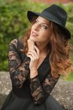 Charming young light brown hair brunette woman with big black hat and blouse with lace sleeves. gorgeous young woman with cur. Ly hair posing. Beautiful portrait stock photo