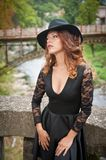 Charming young light brown hair brunette woman with big black hat and blouse with lace sleeves. gorgeous young woman with cur. Ly hair posing. Beautiful portrait stock images