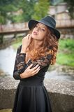 Charming young light brown hair brunette woman with big black hat and blouse with lace sleeves. gorgeous young woman with cur. Ly hair posing. Beautiful portrait stock photography