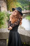 Charming young light brown hair brunette woman with big black hat and blouse with lace sleeves. gorgeous young woman with cur. Ly hair posing. Beautiful portrait royalty free stock image