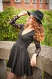Charming young light brown hair brunette woman with big black hat and blouse with lace sleeves. gorgeous young woman with cur. Ly hair posing. Beautiful portrait royalty free stock images