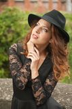 Charming young light brown hair brunette woman with big black hat and blouse with lace sleeves. gorgeous young woman with cur. Ly hair posing. Beautiful portrait stock image
