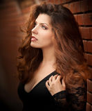 Charming young light brown hair brunette woman in black blouse near a red brick wall. gorgeous young woman. With long curly hair near old wall. Beautiful stock image