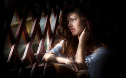 Charming young light brown hair woman looking through wooden grid. Sexy gorgeous young woman with long curly hair staying in rays Royalty Free Stock Photos