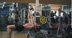 A charming young man with a beard and he is very toned, he lifts up a weight over his head and works out on his lower. Biceps. 4k stock video