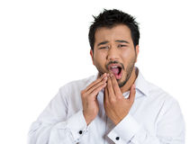 A charming young man crying out in pain because of a dental infection Royalty Free Stock Images