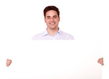 Charming young man holding a blank placard Royalty Free Stock Images
