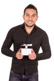 Charming young man holding a gift box. Isolated on white Stock Photo
