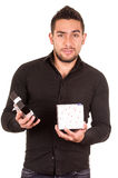 Charming young man holding a gift box looking. Disappointed isolated on white Stock Image