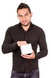 Charming young man holding a gift box looking. Disappointed  on white Stock Photo