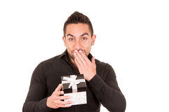 Charming young man holding a gift box. Looking happily surprised isolated on white Royalty Free Stock Photography