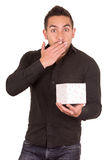 Charming young man holding a gift box looking. Surprised isolated on white Stock Photography