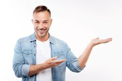 Charming young man presenting something. Making presentation. The portrait of a pleasant cheerful young man stretching his hands and pointing at something as if Stock Photography
