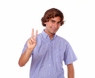 Charming young man showing you victory sign Royalty Free Stock Image