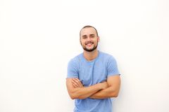 Charming young man smiling. Against white background with arms crossed Royalty Free Stock Images