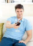 Charming young man on a sofa holding wineglass Royalty Free Stock Images