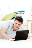 Charming young man using his laptop on the floor Stock Photography