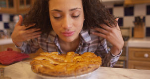 Charming young mixed ethnic woman smelling apple pie royalty free stock photos