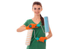 Charming young slim builder girl makes renovations with paint roller isolated on white background Royalty Free Stock Images