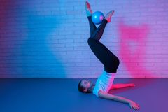 Charming young slim gymnast woman in sports clothing exercises in front of brick wall in neon lights. Flexible fit woman royalty free stock photos