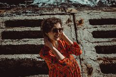 Charming young smiling woman in red dress with short curly hair looking at camera. Female retro sun protection sunglasses. Enjoy stock photography