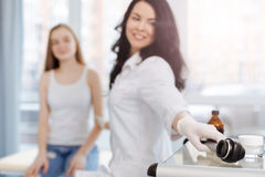 Charming young specialist using dermatoscope for skin examination at work Stock Image