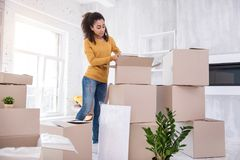 Charming young student packing belongings before moving out. Bye residence. Charming curly-haired student packing her belongings into boxes while moving out of stock photo