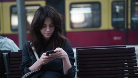 Charming young tourist texting on a bench in the Berlin Central Train Station. Charming young brunette tourist texting while sitting on a bench in the Berlin stock footage