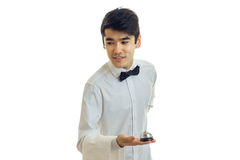Charming young waiter holding a Bell and leans forward Stock Photography