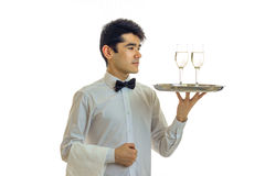 Charming young waiter stands evenly and neatly holds a tray with glasses of white wine is isolated on a white background. Close-up Royalty Free Stock Image