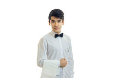 Charming young waiter stands upright in a white shirt and keeps on hand a towel Royalty Free Stock Photos