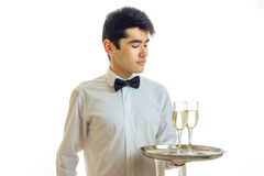 Charming young waiter in a white shirt and with a butterfly holding a tray with two glasses of champagne Stock Images