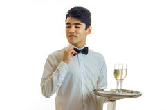 Charming young waiter in a white shirt holding a tray with glasses of wine and adjusts his bow tie hand. Isolated on white background Stock Images
