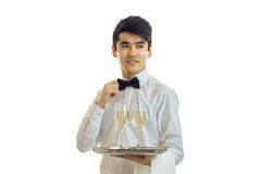 Charming young waiter in a white shirt smiling keeps the tray with glasses of wine and adjusts his bow tie at the neck Royalty Free Stock Photo