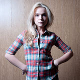 Charming young woman. Young charming woman in shirt on a wooden background Royalty Free Stock Photography