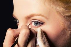 Charming young woman applying blusher eyelid Stock Photography