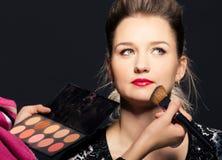 Charming young woman applying blusher eyelid Stock Image
