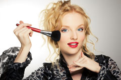 Charming young woman applying brush Royalty Free Stock Images