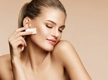 Charming young woman applying foundation on her face using makeup sponge. Photo of attractive woman with perfect skin on beige background. Youth and skin care stock photos