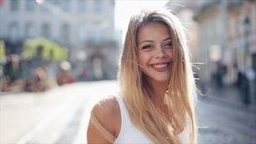 Charming young woman with a in a beautiful white dress with loose hair. Attractive young lady is rushing in the city. Center, she turns to camera and smiles stock video footage
