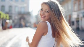 Charming young woman with a in a beautiful white dress with loose hair. Attractive young lady is rushing in the city. Center, she turns to camera and smiles stock video