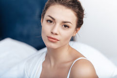 Charming young woman in bed. Close-up portrait of charming young woman in bed Royalty Free Stock Image