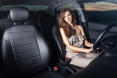 Charming young woman behind the wheel looking at the camera shot through the glass Outdoors Royalty Free Stock Photo
