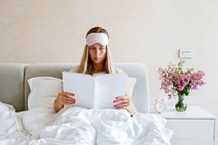 Charming young woman with blindfold on her head reading fashion magazine in bed. Bedroom decor with bouquet of flowers, alarm stock photo